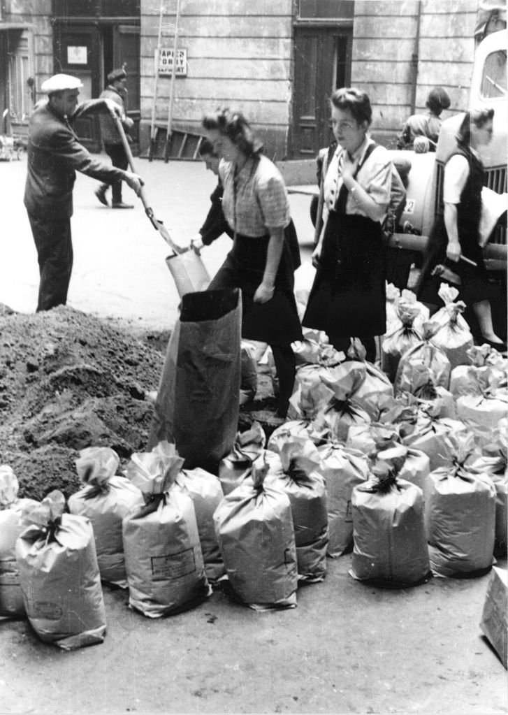 Filling sand bags. August 1944. Via Wikimedia Commons.