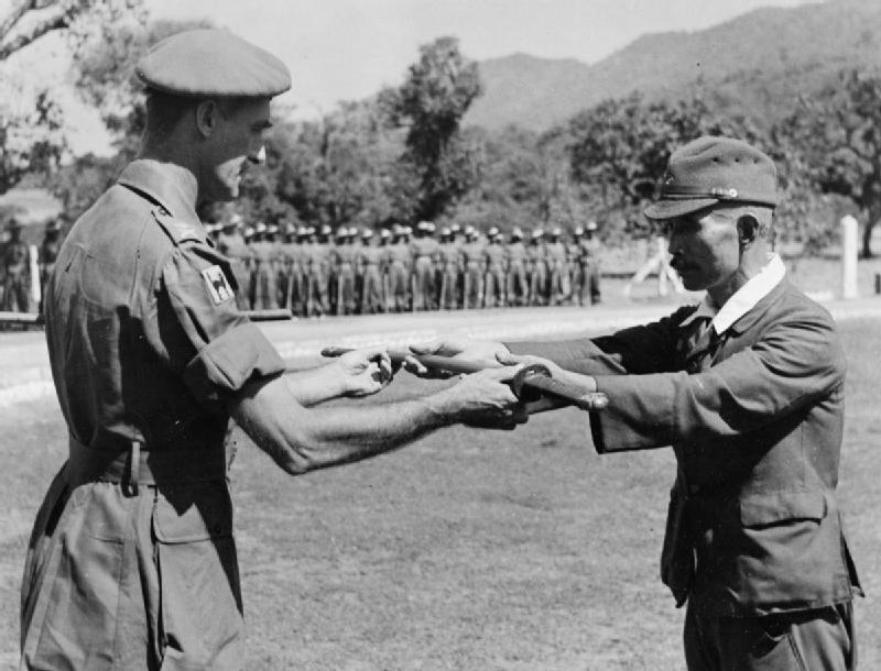 A Japanese general surrenders his sword in 1945. Via Wikimedia Commons.
