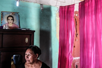 Doña Julia Caldera Chávez stands in her home in front of the only portrait of her daughter María Elena on the 15th anniversary of the discovery of María Elena's body. She disappeared from Juárez on June 20, 2000 and her body was discovered on October 24 of that same year. Her murder remains unresolved. Photo: Alice Driver