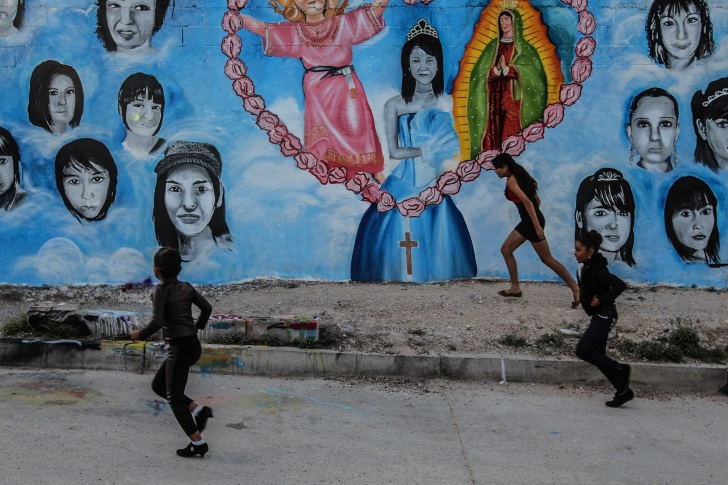 Schoolgirls walk in front of a mural painted with the faces of disappeared girls. Local artists and families of the disappeared have been working together to raise awareness about disappearance in Juárez; they paint the faces of missing girls on the donated walls of schools, churches, and homes around the city. Photo: Alice Driver