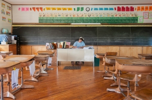 A teacher from an Amish one room school house corrects papers after a day with her students. Photo: Tessa Smucker