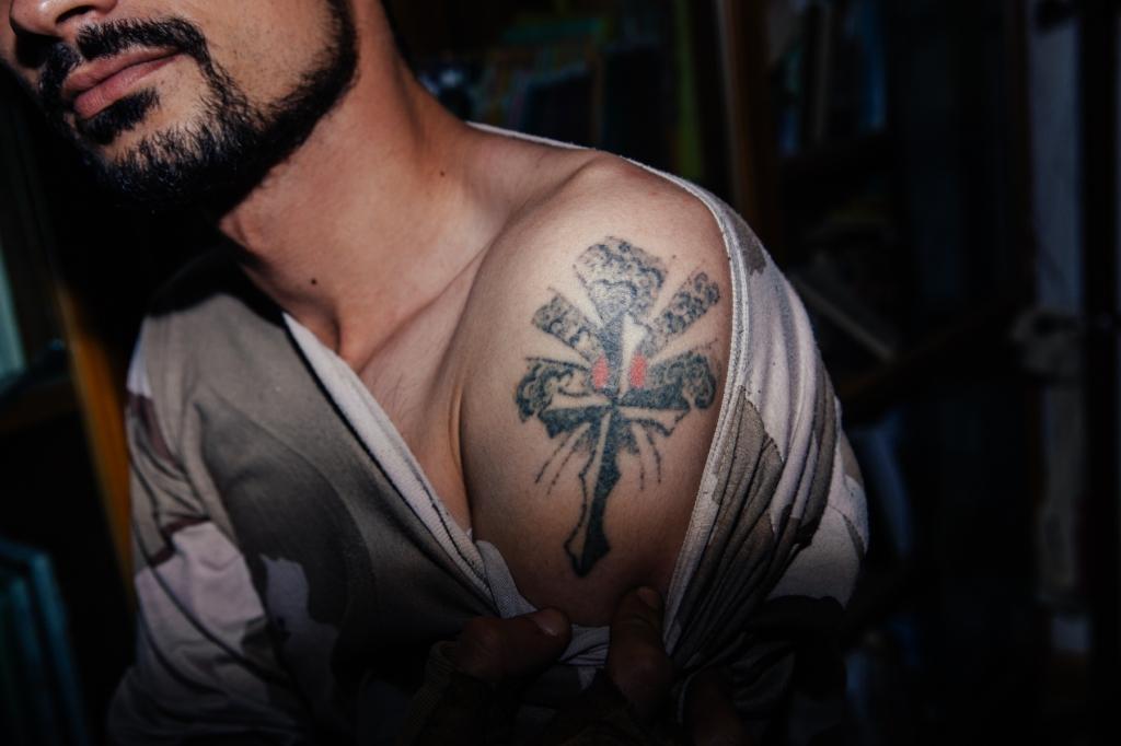 A Dwekh Nawsha soldier in Bakufa shows his Christian tattoo. Photo by: Erin Trieb