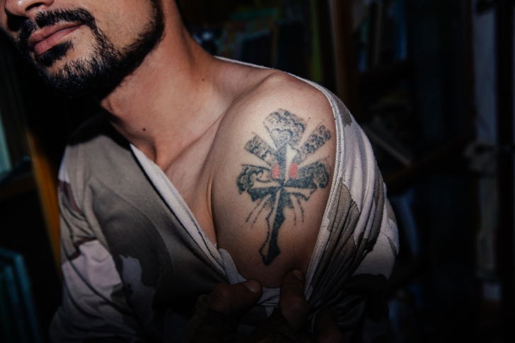 A Dwekh Nawsha soldier in Bakufa shows his Christian tattoo. Photo by: Erin Trieb