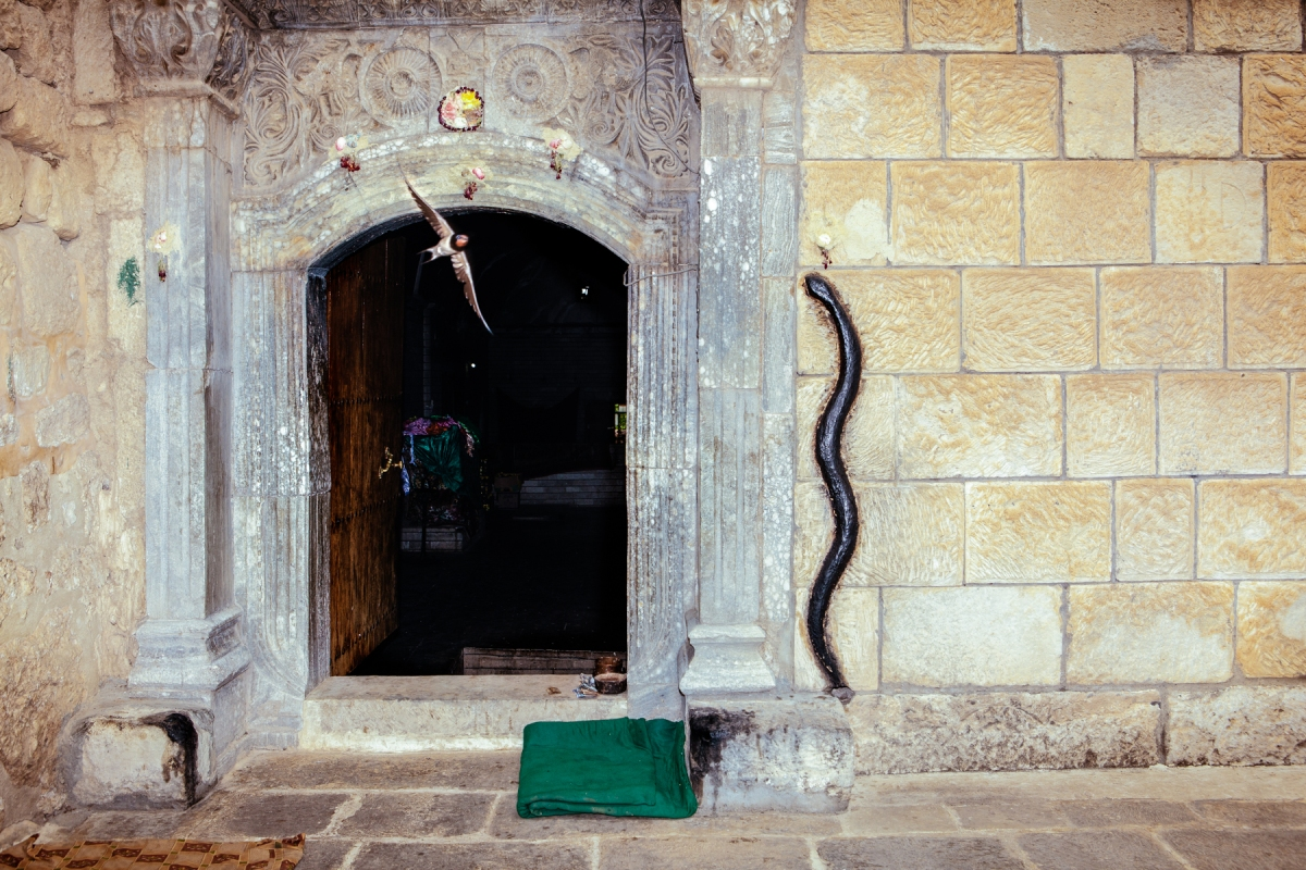 A bird flies out of Lalish temple which features a stone black snake on its wall. Photo by: Erin Trieb