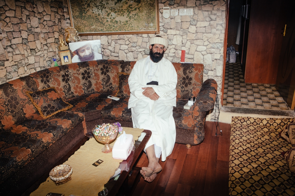 """""""Baba"""", a Yezidi high priest, sits in his living room in Lalish. Photo by: Erin Trieb"""