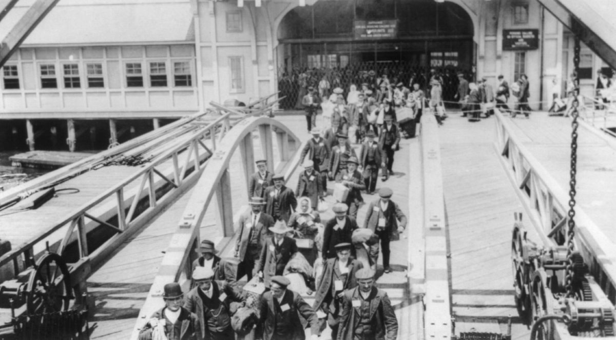 Immigrants walking across the pier at Ellis Island, early 20th century. LIBRARY OF CONGRESS/LC-USZ62-95433
