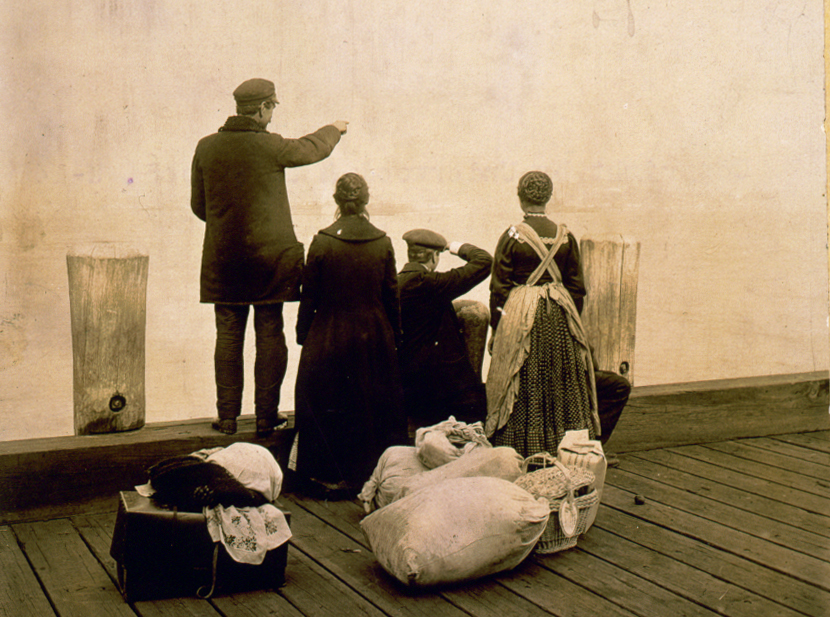 Four immigrants and their belongings, on a dock, looking out over the water at Ellis Island, 1912. LIBRARY OF CONGRESS/LC-USZC4-5584