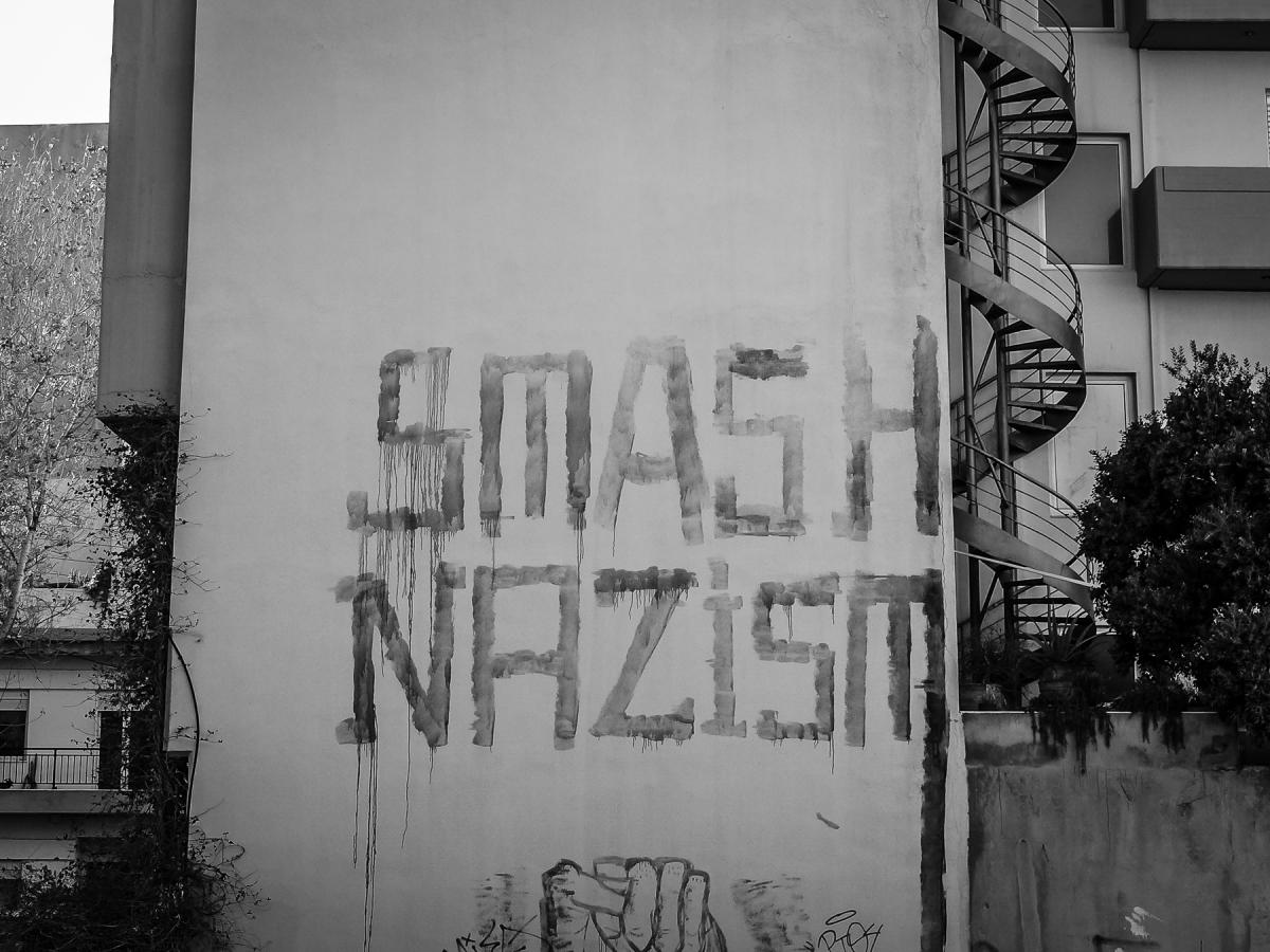 "Graffiti reading ""Smash Nazism"" on a concrete wall."