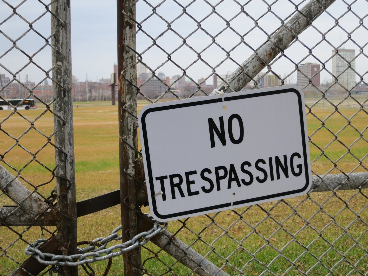 "a ""no trespassing sign"" hangs on a padlocked fence"