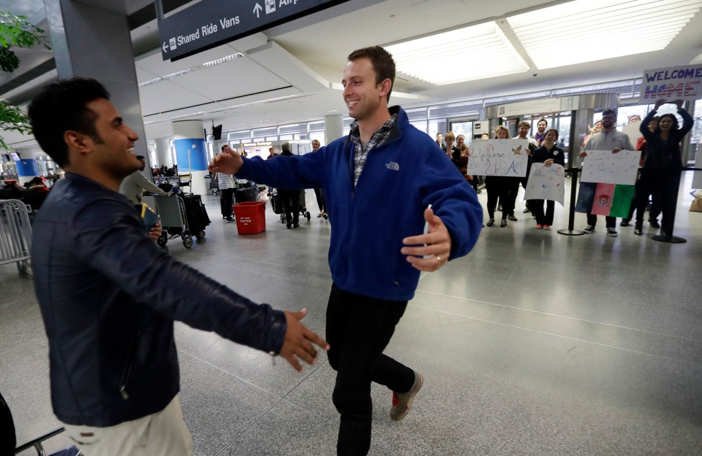 Army Capt. Matthew Ball, right, prepares to hug his former interpreter Qismat Amin, as Amin arrives from Afghanistan, at San Francisco International Airport Wednesday, Feb. 8, 2017, in San Francisco. Ball welcomed Amin to the United States after buying him a plane ticket to ensure he would get in quickly amid concerns the Trump administration may expand its travel ban to Afghanistan. (AP Photo/Marcio Jose Sanchez)