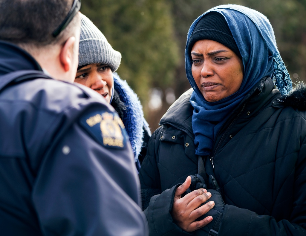 Two people who told the Royal Canadian Mounted Police they are from Sudan speak with an officer after crossing into Canada from Perry Mills, N.Y., near Hemmingford, Quebec, Sunday, Feb. 26, 2017. (AP Photo/Craig Ruttle)