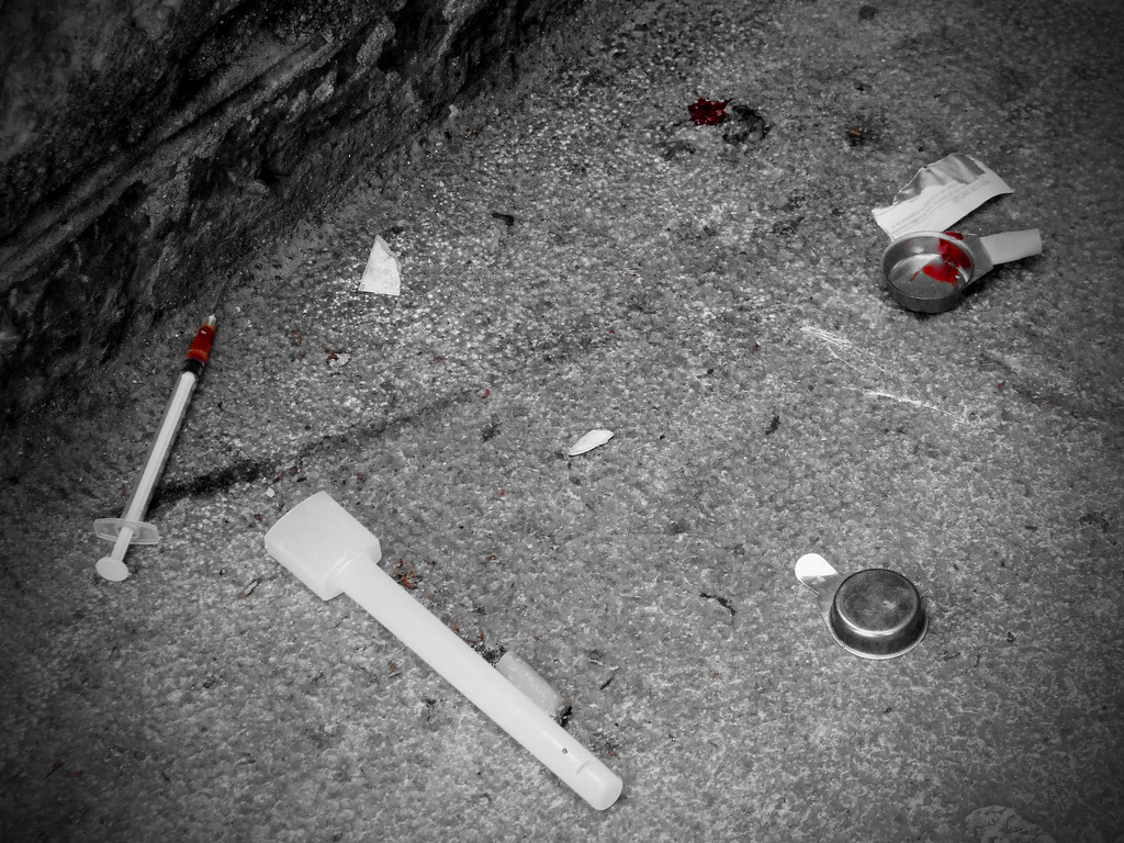 drug parephenalia scattered on a sidewalk, black and white photo with splashes of red