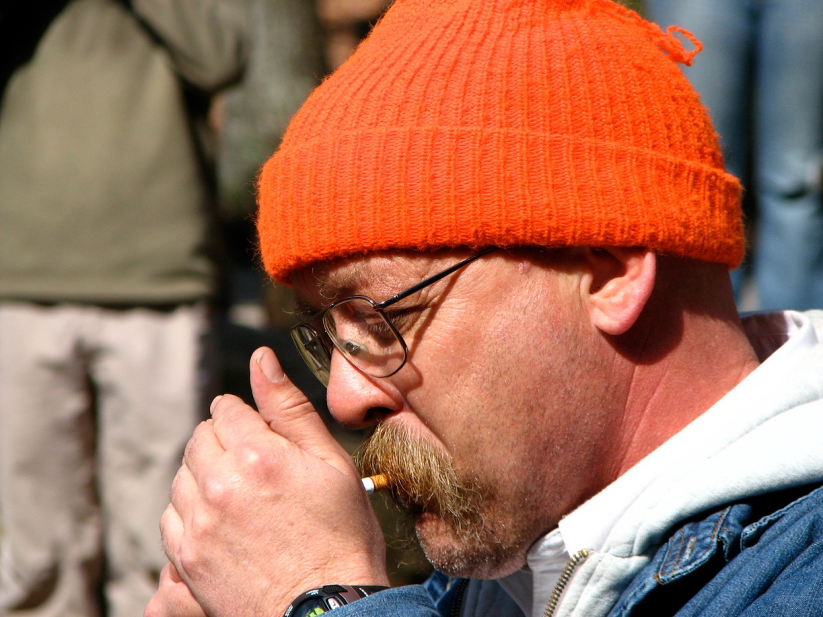 a man in an orange knit hat lights a cigarette
