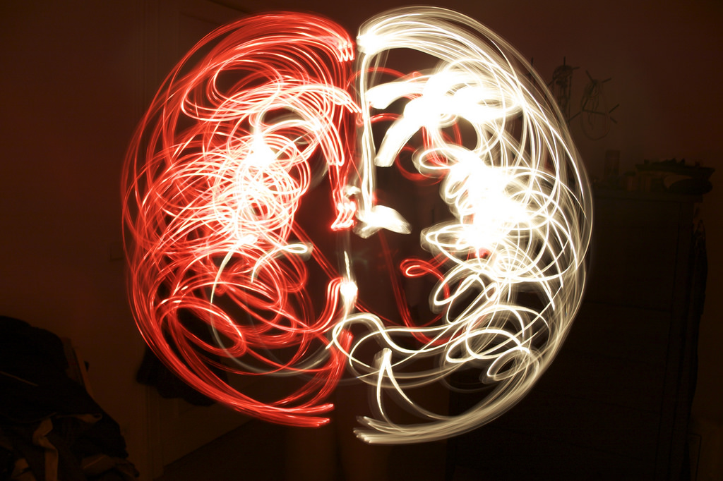 a drawing of a human brain, made with streaks of red and white light