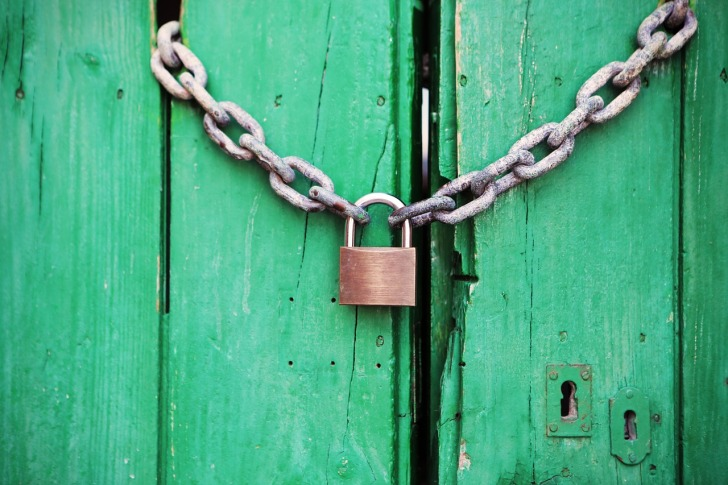 Padlock and chain on a green wooden door with keyholes