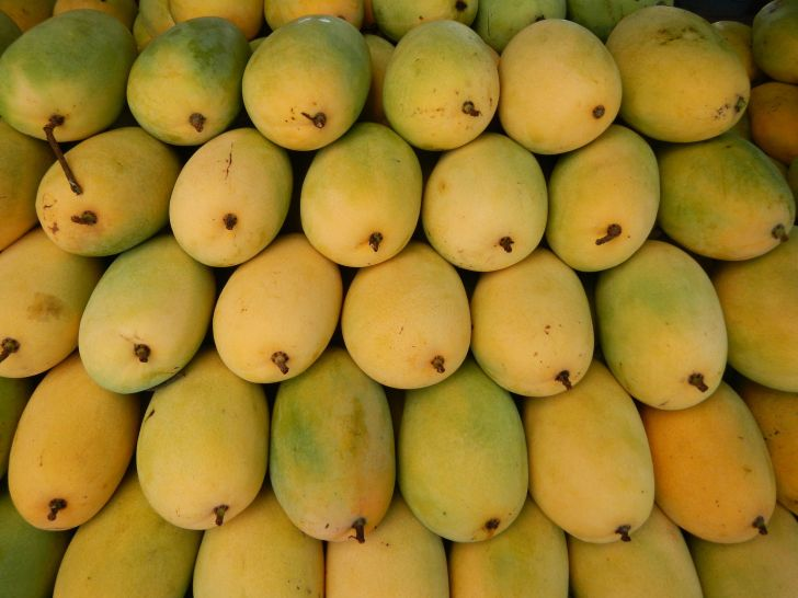 a stack of yellow mangoes