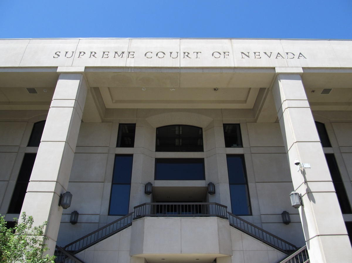 the front of the supreme court of nevada, a large door flanked by stairs and pillars