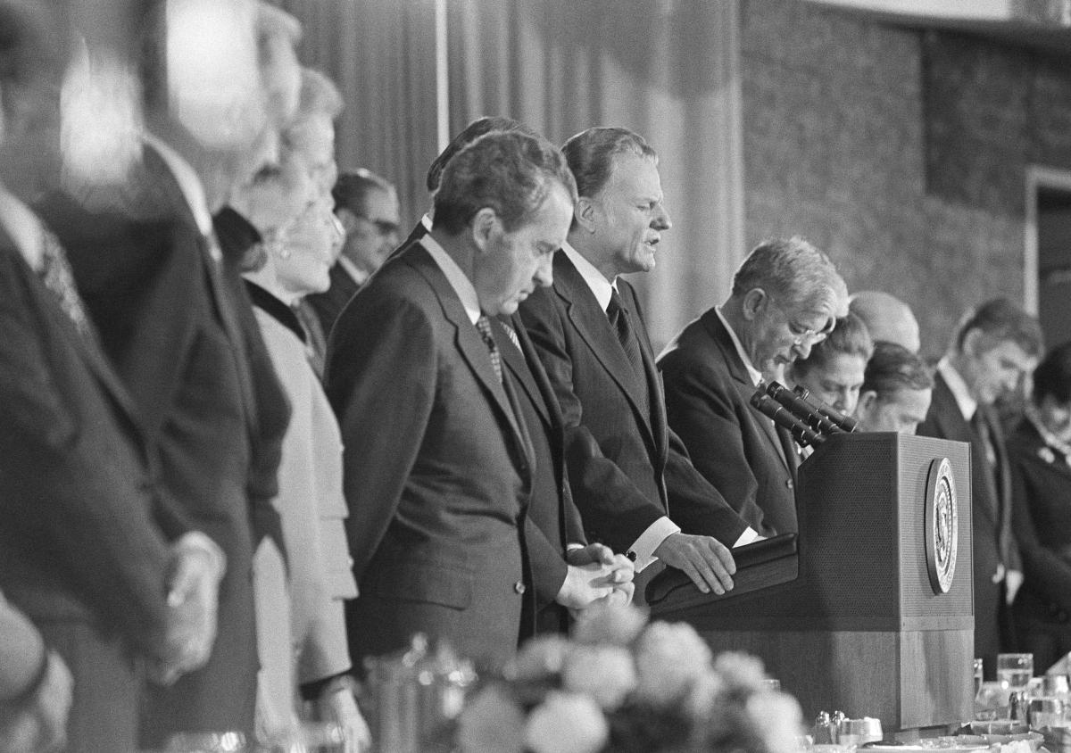 Rev. Billy Graham gives the closing prayer at Nixon's National Prayer Breakfast in 1973. (AP Photo)