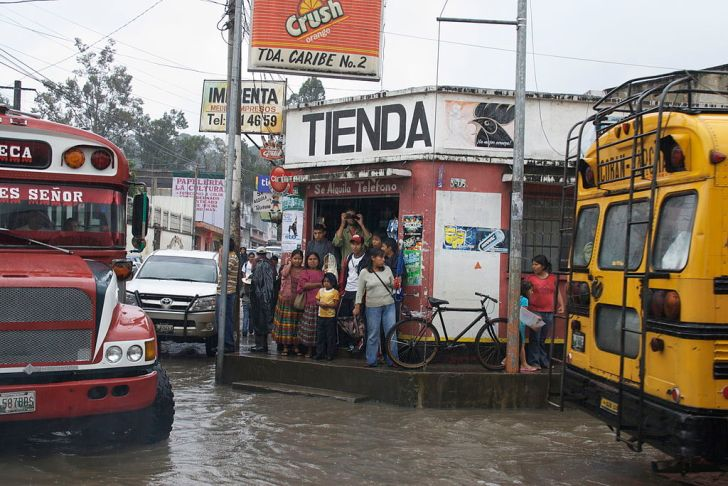 People standing in a shop to get out of the rain at a Guatemala bus station