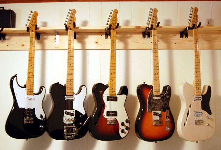 Fender Telecaster guitars hanging on a wall rack.