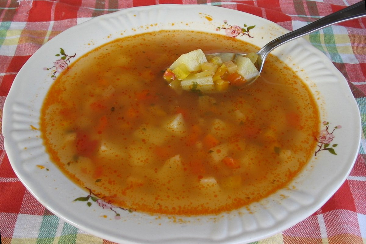 a bowl of vegetable soup with a spoon in it