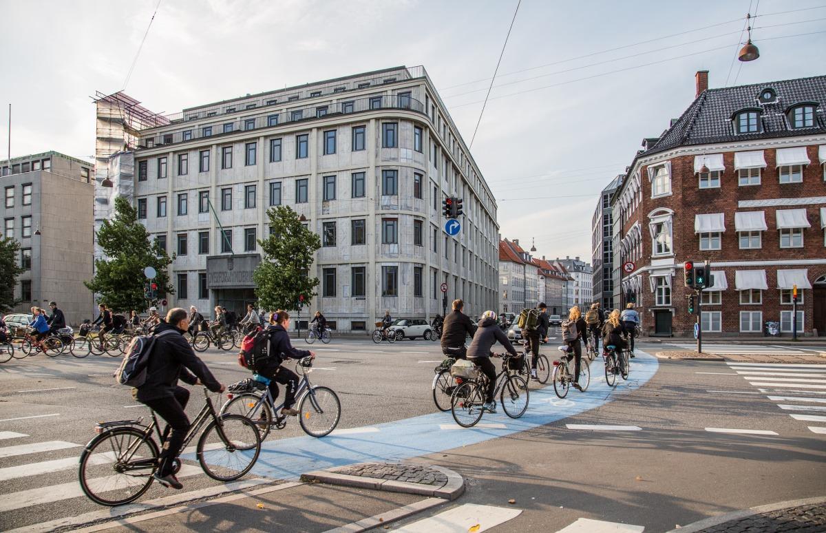 cyclists ride along a blue bike path in copenhagen, denmark