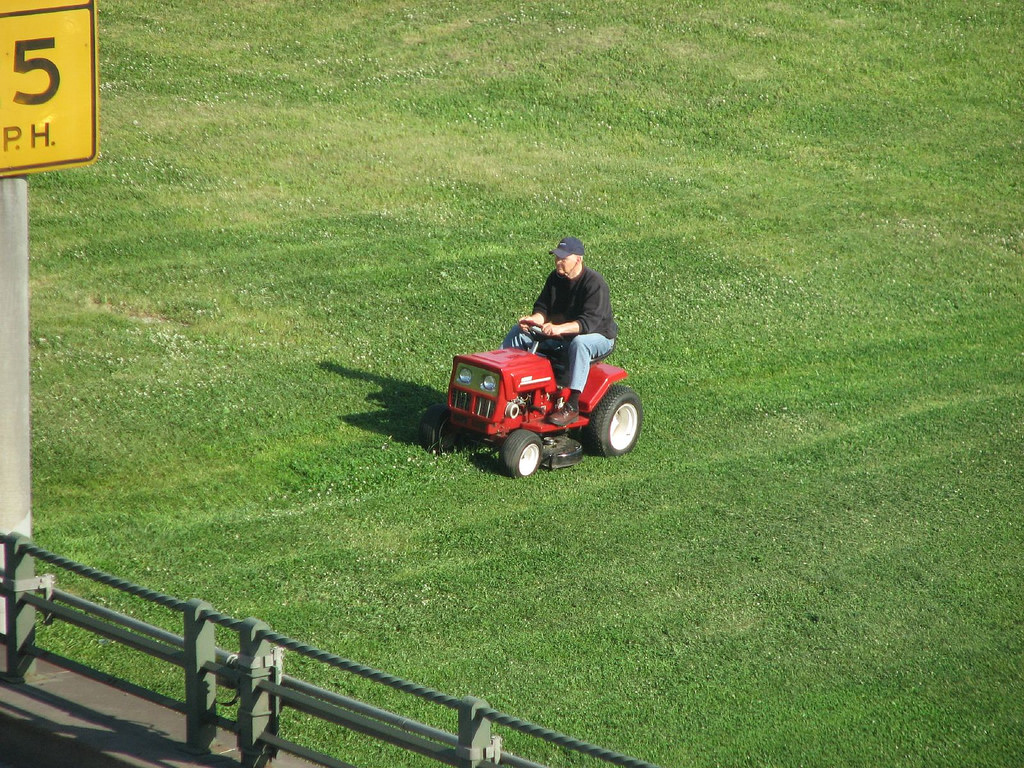 Man on a lawnmower on a large swath of grass