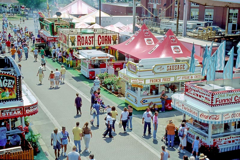 People walking the midway past food stands at a State Fair