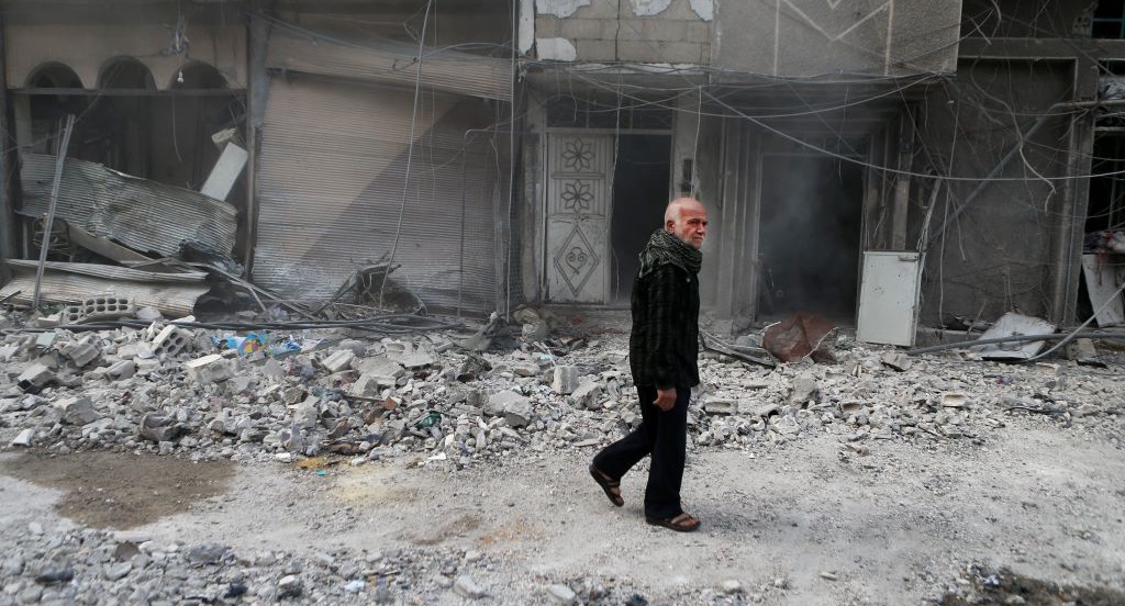 A Syrian man walks through a devastated street following an air strike. (Photo credit: Abdulmonam Eassa / AFP / Getty Images)