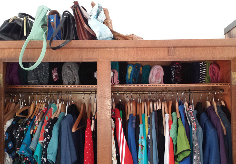 rows of colorful shirts hanging in a closet. six leather handbags sit on a shelf above.