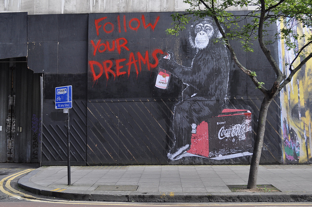 "graffiti on a wall showing a monkey holding a can of red spray paint, with the words ""follow your dreams"""