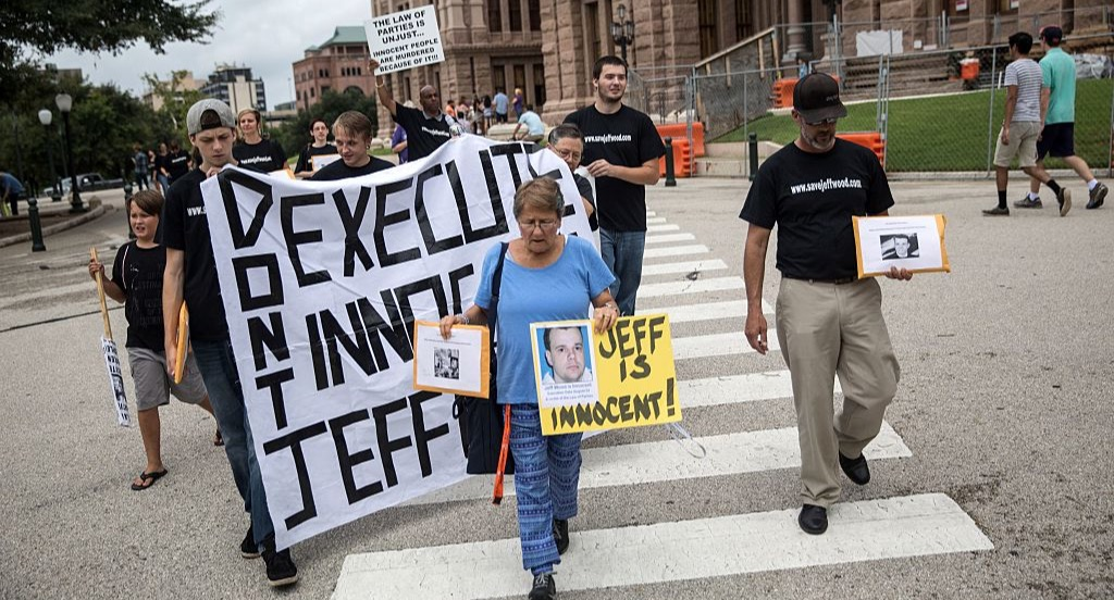 Anti-death penalty activists march with a sign to free Jeff Wood