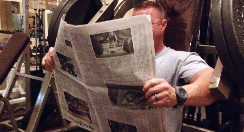 Bodybuilder reading the Paper Upside Down