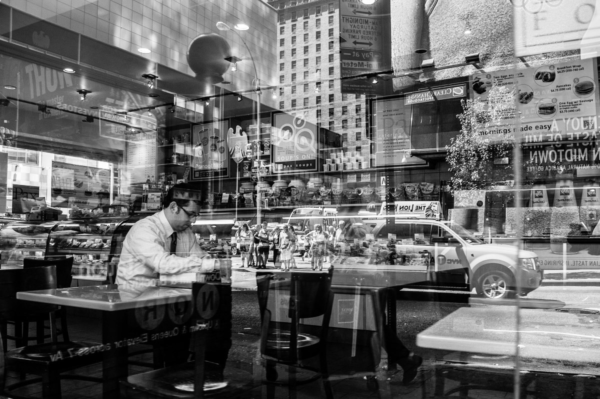 a man in a restaurant seen through a window, eating alone. the people and cars of the city are reflected in the window.