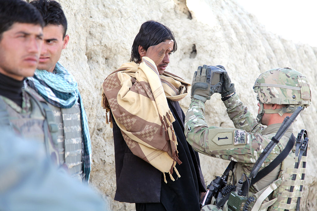A U.S. soldier uses a handheld tool to scan the retinas of military-aged males in Paktika Province, Afghanistan.