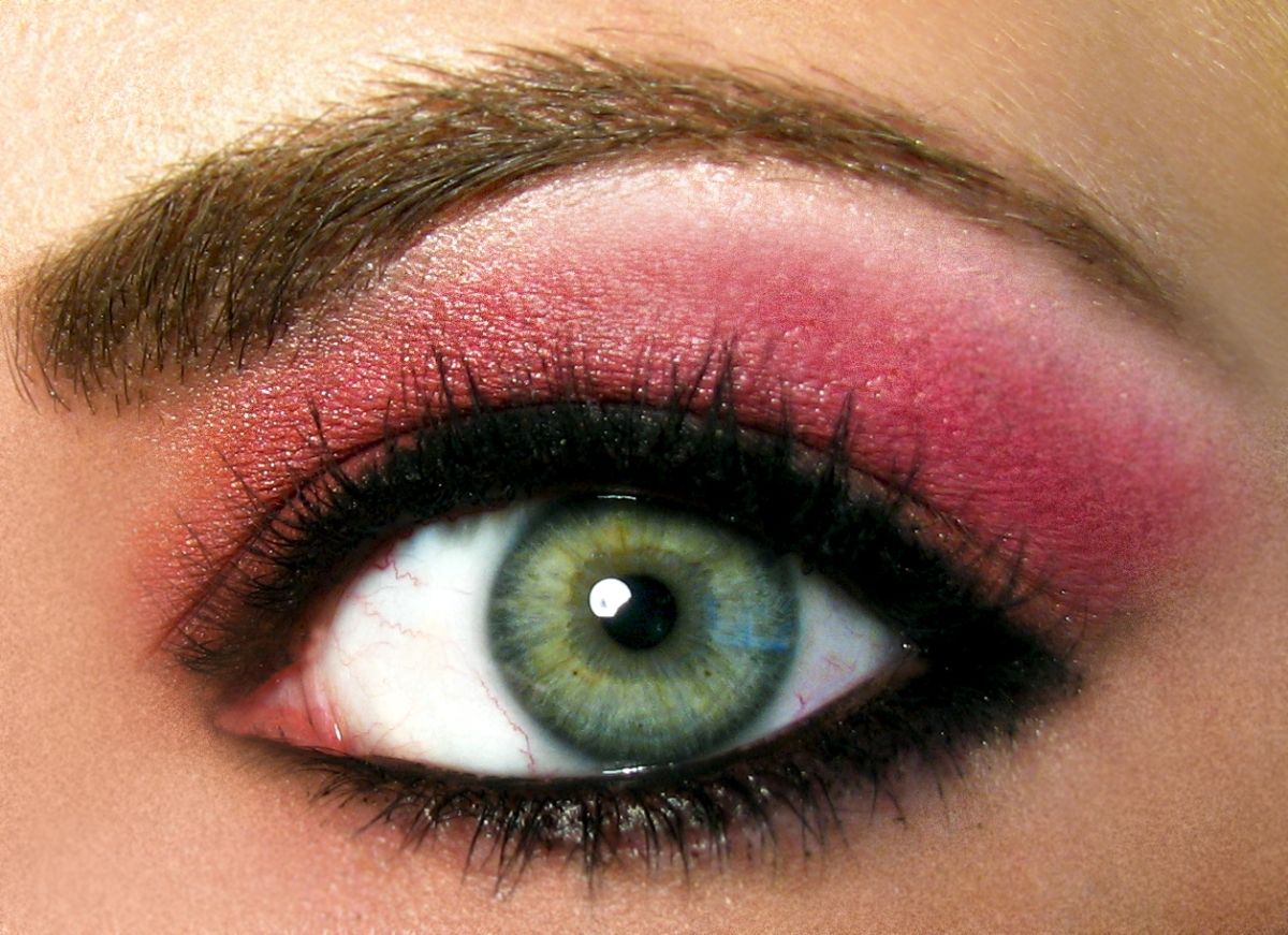 closeup of a green eye, heavily made up with deep pink eyeshadow