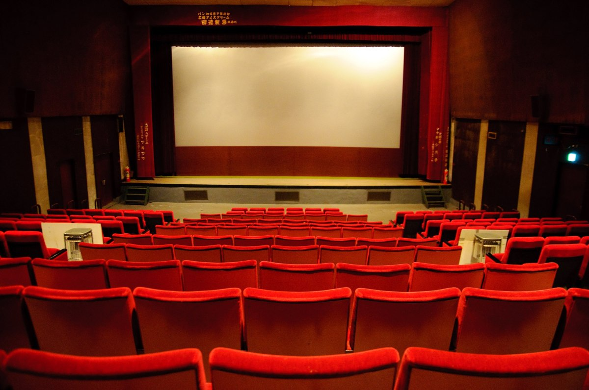 In a movie theater, rows of red velvet chairs sitting empty in front of a blank screen.