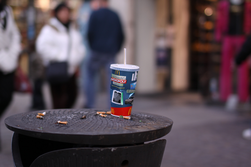 A cardboard soda cup from McDonald's sits on top of a black garbage can, surrounded by cigarette butts