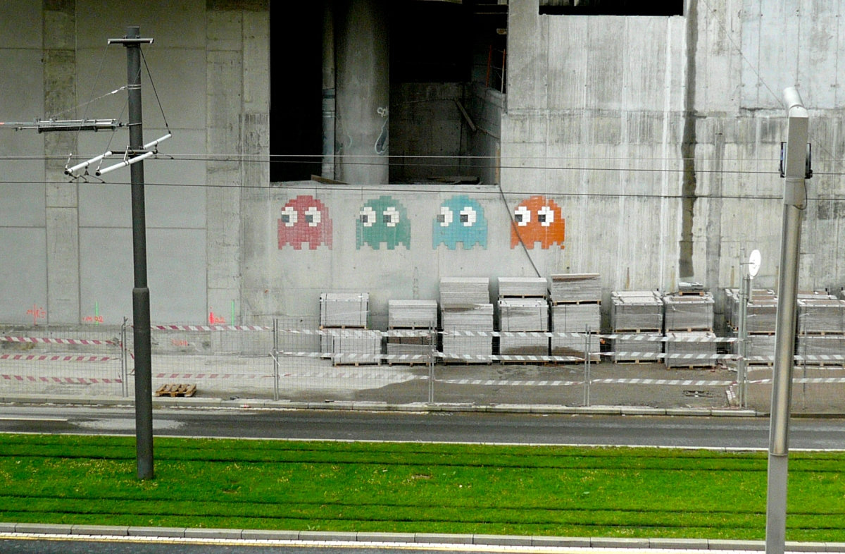 red, green, blue, and orange pac-man ghosts painted on a gray wall, with bright green grass on the ground
