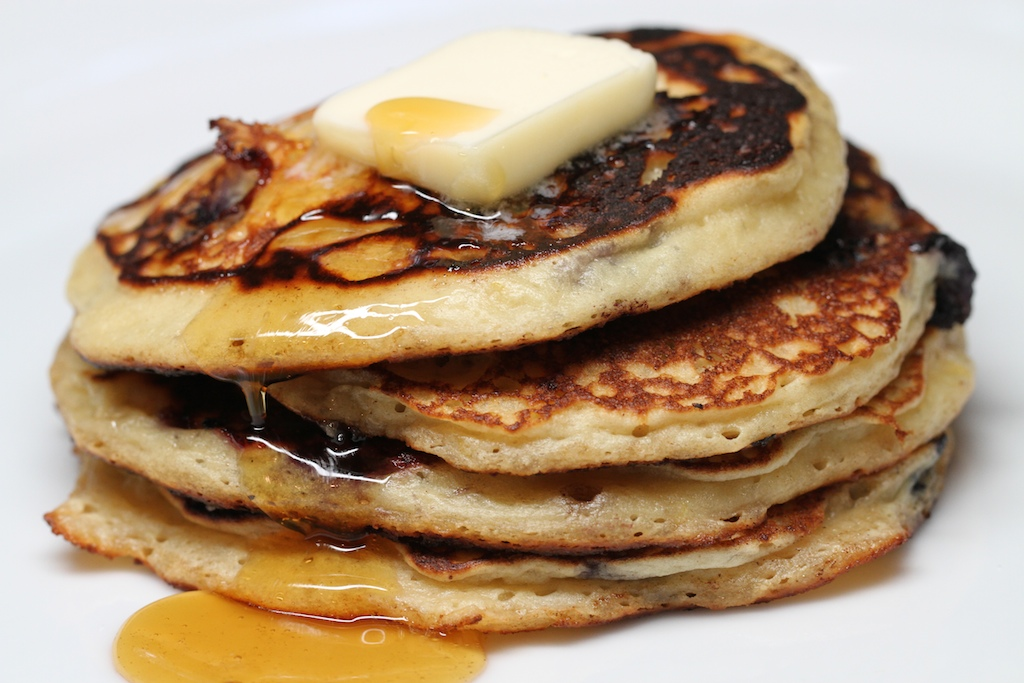 a stack of four pancakes. there is a pat of butter on the top and maple syrup dripping down the side.