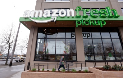 An Amazon worker wheels back a cart after loading a bag of groceries into a customer's car at an AmazonFresh Pickup location in Seattle. (AP Photo/Elaine Thompson, File)