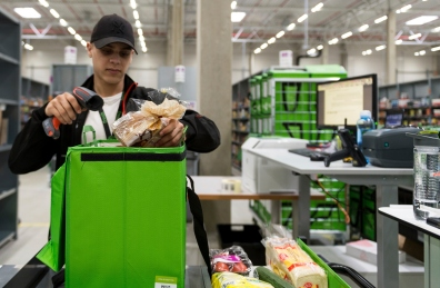 An employee of grocery delivery service Amazon Fresh scans ordered products before putting them into a transport bag. (Monika Skolimowska/picture-alliance/dpa/AP Images)