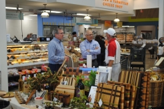 Harvest Market executives Gerry Kettler, left, and Rich Niemann chat with a salsa vendor visiting to do demos. (Photo courtesy of the author.)