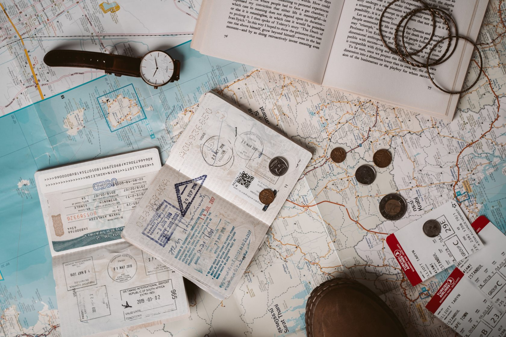 Passport and travel documents, a watch, an open book, and coins on top of paper maps